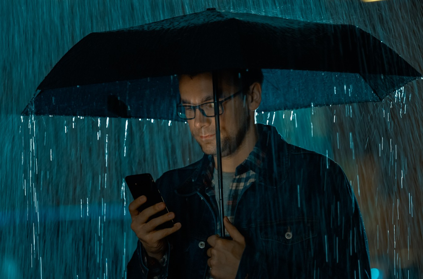 Man in Glasses, Wearing a Jeans Coat and Square Shirt is Using a Smartphone Under an Umbrella