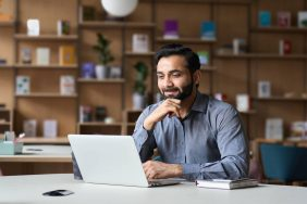 Smiling indian businessman working on laptop in modern office lobby space