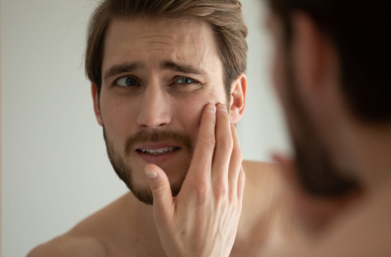 Close up head shot unhappy man looking in mirror, feeling stressed of sensitive skin