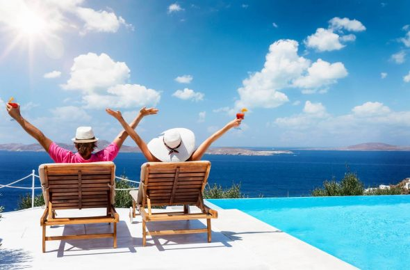 Happy vacation couple sitting on sunchairs by the pool